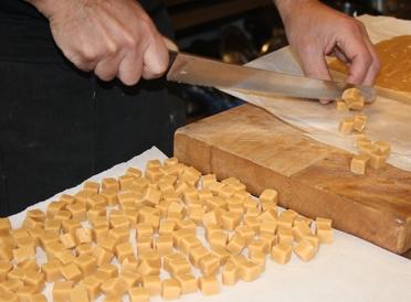 Johan skär vår underbart goda smörkola fudge
